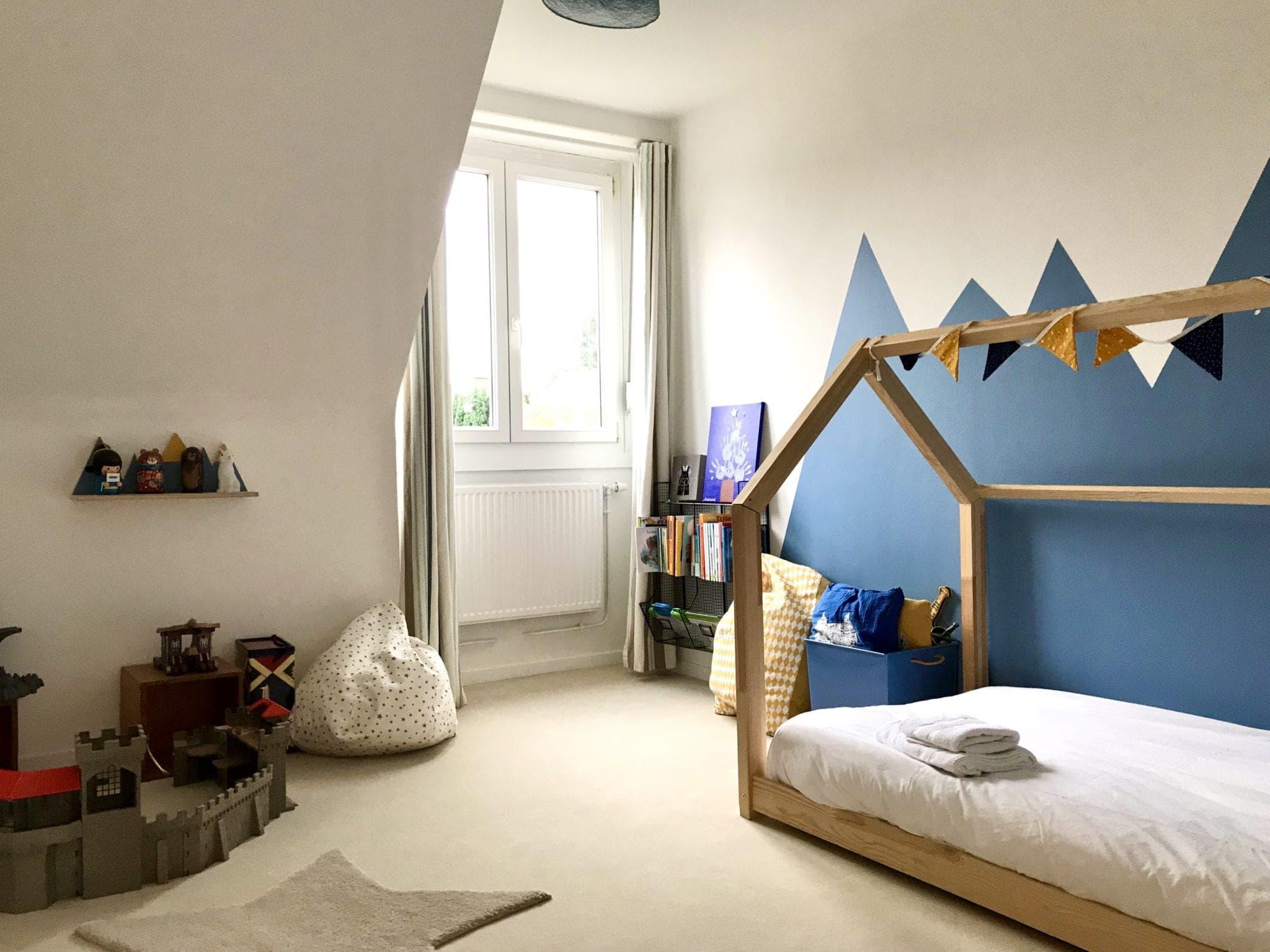 chambre d'enfant avec lit cabane et montagnes en peinture